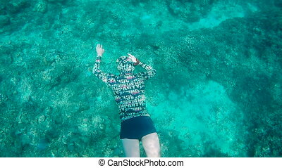 Diver swims under water on the ocean floor and then rises to the surface to breathe air. Tourist engaged diving near a exotic islands.