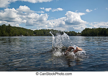 A pair of feet is still visible after a swimmer has dived into the lake. Blue sky and trees in the background.