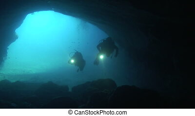 Divers in a cave - Divers are exploring the entrance of a...