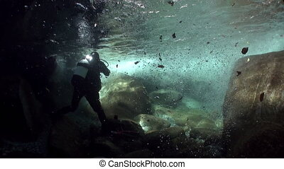 Divers with camera underwater in mountain river Verzasca.