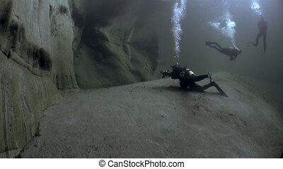 Divers with camera underwater in transparent river Verzasca....