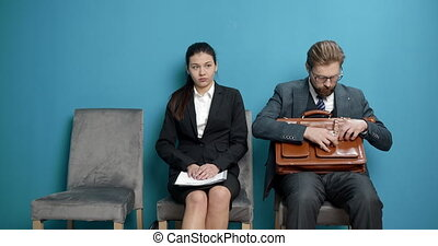 Diverse applicants waiting in blue hall for job interview - ...