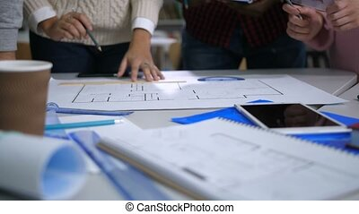 Diverse architects working on blueprint in office