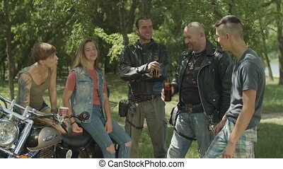 Diverse bikers relaxing after motorbike ride - Group of...