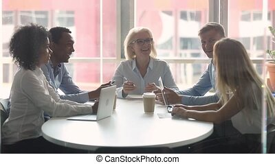 Diverse business people gathered in modern boardroom for...
