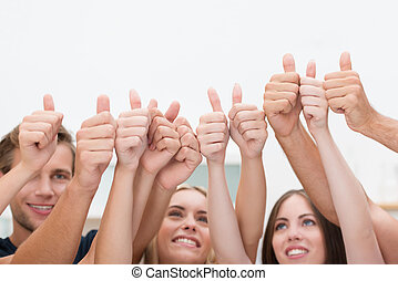 Diverse business people giving a thumbs up