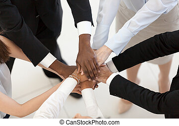 Diverse business people put hands together in pile, top view