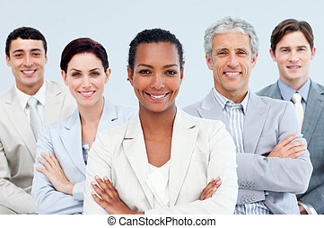 Diverse business people standing with folded arms smiling at...