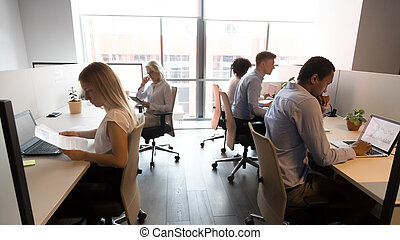 Diverse business people working in office, using computers, workday