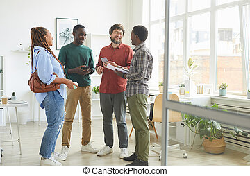 Full length portrait of multi-ethnic group of people dressed in casual wear and smiling cheerfully while discussing work standing in office