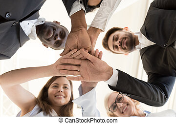 Diverse business team put hands together as concept of teambuild