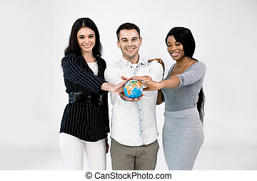 diverse business team, students, coworkers, Caucasian and African women, Caucasian man, holding a terrestrial globe, posing over white background. International cooperation, travel, study concept