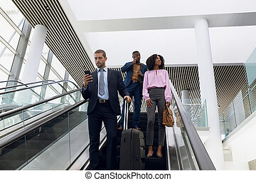 Diverse business travellers on an escalator