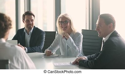 Diverse businessman and businesswoman sit around boardroom table negotiation