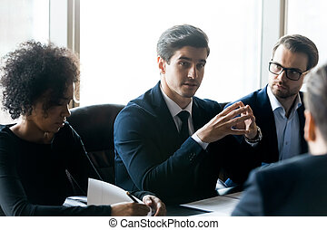 Diverse businesspeople discussing project strategy at meeting in boardroom
