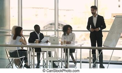 Diverse businesspeople sitting at table listening business coach during training