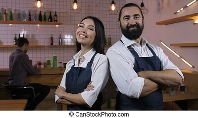 Diverse cafe owners with folded hands smiling - Portrait of...