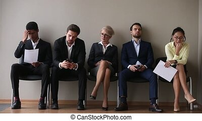 Diverse candidates for vacancy sitting on chairs waiting...