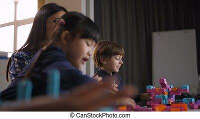 Diverse children building construction toy blocks