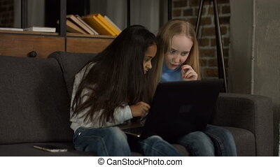 Diverse children surfing the net on laptop at home -...