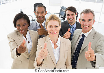 Diverse close business team smiling up at camera giving thumbs up in the office
