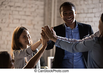 Diverse colleagues give high five celebrating business success