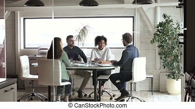 Diverse colleagues or partners handshaking negotiating in modern meeting room