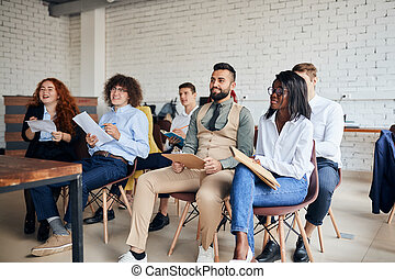 Diverse colleagues sit on business training with coach