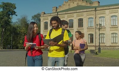 Diverse college students walking to class outdoors