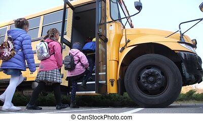 Diverse elementary age kids getting on school bus - Lined up...