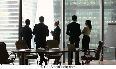 Diverse employees group stand separately talking at work,...