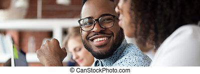 Diverse employees working in shared office focus on african guy