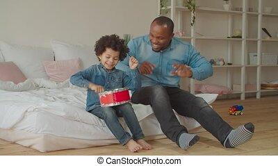 Diverse family enjoying leisure playing toy drum