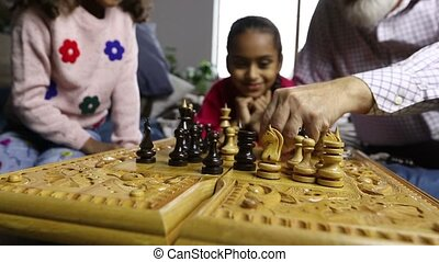 Diverse family playing chess together at home