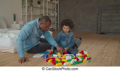 Diverse family playing with constructor at home