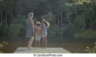 Diverse family standing on wooden jetty by lake - Rear view...