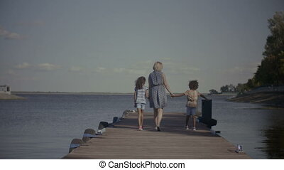 Diverse family walking on wooden pier in summer - Positive...