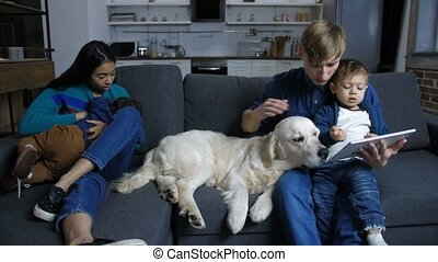 Diverse family with labrador dog relaxing at home - Caring...