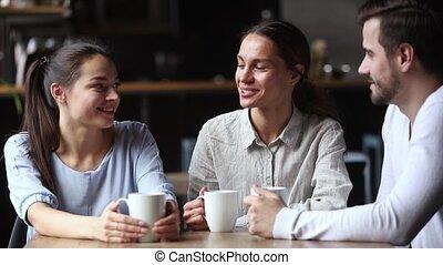 Diverse friends drinks tea talking spending time in cafe -...