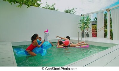 Diverse friends enjoying leisure in swimming pool