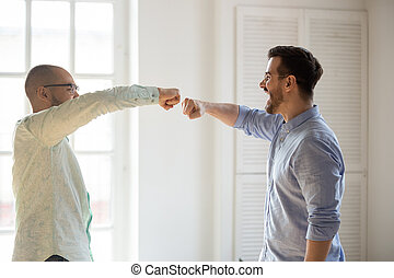 Diverse friends fists bumping, celebrating success, greeting at meeting