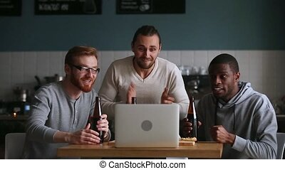 Diverse friends hangout in pub watching online match at...