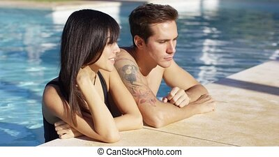 Diverse good looking couple stand in swimming pool with...