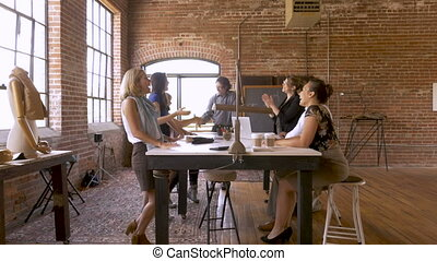 Diverse group of attractive women and men shaking hands in an office