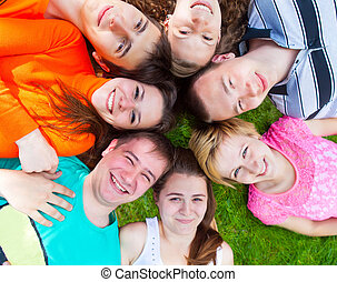Diverse group of friends outside lying on a lawn