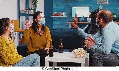 Diverse group of funny people in living room playing Who am I game with sticky papers attached to foreheads during global pandemic wearing protection masks. Friends socializing in outbreak