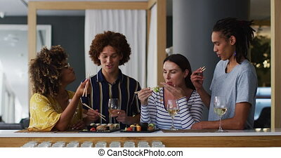Diverse group of happy friends drinking wine eating sushi and talking at a bar