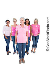 Diverse group of happy women wearing pink tops and breast cancer ribbons on white background