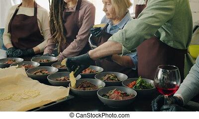 Diverse group of joyful people preparing and serving tasty meals in cookery school