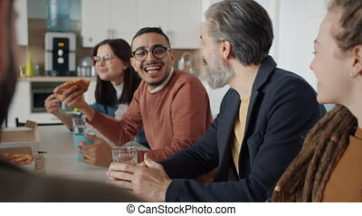 Diverse group of people coworkers are talking and laughing eating pizza in workplace enjoying work break together. Emotions and business concept.